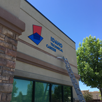 Sinage at the Idaho Technical Career Academy (ITCA) being placed onto their building campus. The name of the school along with the logo, two intersecting places, one red and the other blue, adorn the building.